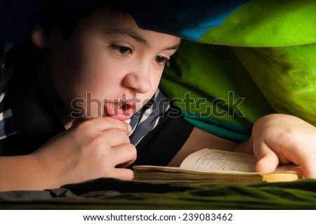 boy reading a book under the covers  - stock photo