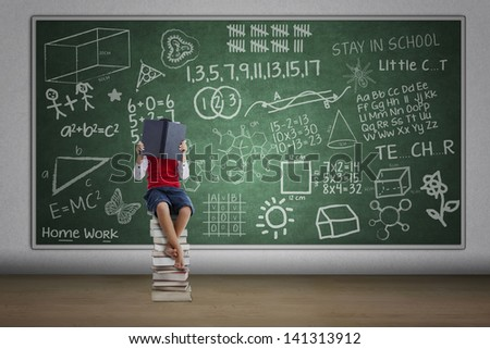 Boy reading book in class sitting on stack of books with written chalkboard - stock photo