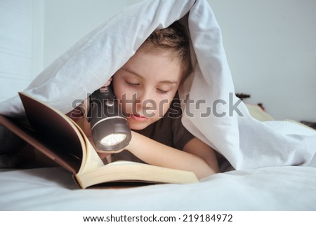Boy reading under the covers - stock photo