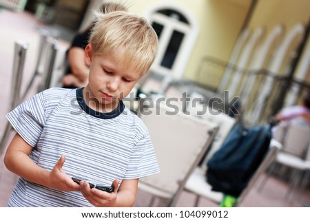 Boy reads SMS message at mobile phone. - stock photo