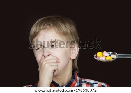 Boy refusing to take medicine on a spoon - stock photo