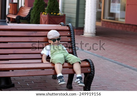 Boy resting on a wooden bench in the city - stock photo