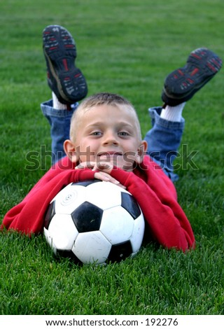 Boy resting on soccer ball. - stock photo