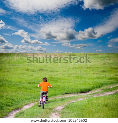 Boy rides a bicycle on a green meadow - stock photo