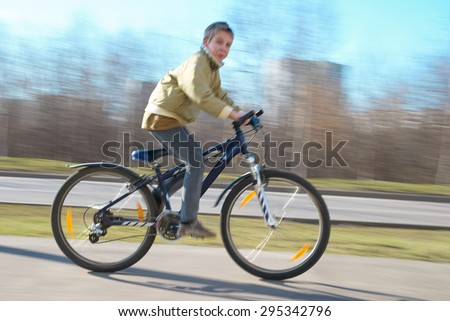 Boy rides very fast on the walkway. The image is blurry because of very high speed - stock photo