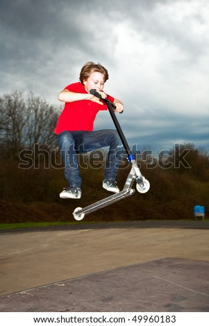 Boy riding a scooter gone airborne on a scooter park - stock photo