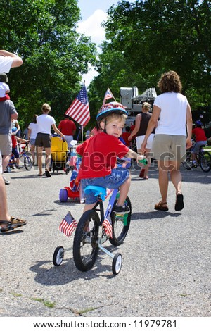 Boy riding his bike in a neighborhood 4th of July parade - stock photo