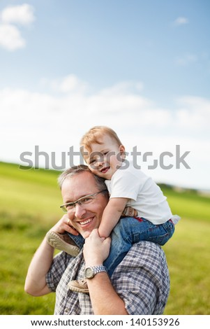 Boy riding his father's shoulders in a field - stock photo