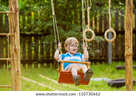 Boy riding on a swing, sunny day