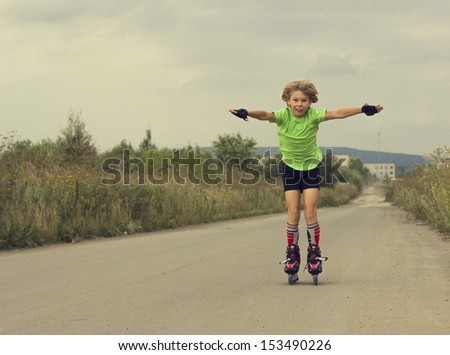 boy riding on rollers on the road near the field - stock photo