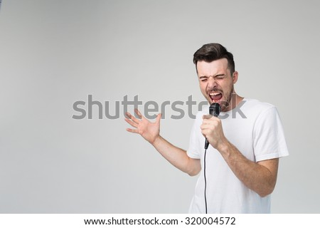 Boy Rocking Out. Image of a handsome man singing to the microphone, isolated on light. Emotional portrait of an attractive guy with a beard on a gray background - stock photo