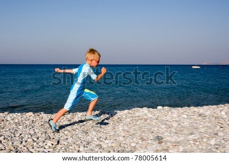 Boy running on gravel beach in summer day