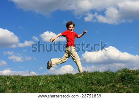 Boy running on green meadow against blue sky - stock photo