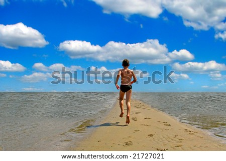 boy running on the beach - stock photo