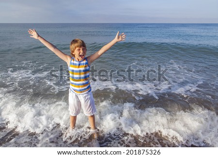 boy running through the water at the beach - stock photo