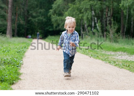 Boy runs on a parks road. Summer - stock photo