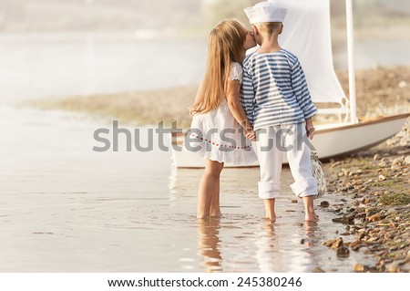 Boy-sailor with a girl walks around the lake on a summer day - stock photo