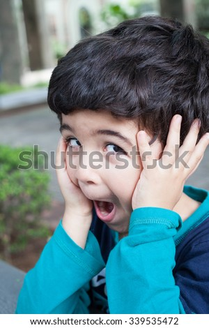 Boy screaming and looking annoyed while holding ears - stock photo