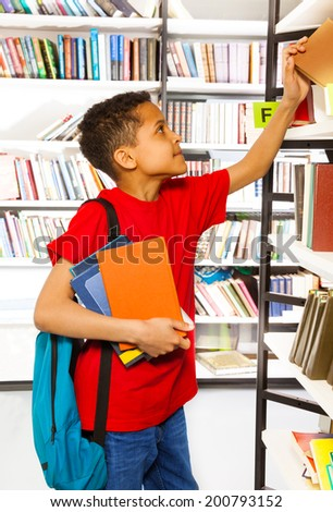 Boy searching books on library bookshelf - stock photo