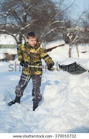 Boy shoveling snow from walkway after hard snowfall - stock photo