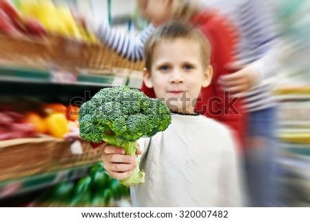 Boy shows broccoli in supermarket - stock photo