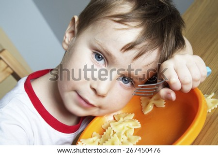 Boy sits at the table, he put his head to the orange plate with pasta - stock photo
