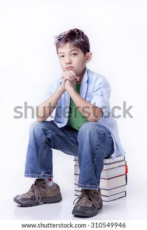 Boy sits on books. - stock photo