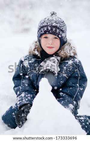 boy sits on the snow and plays with him in the snowfall  - stock photo