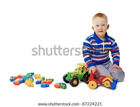 Boy sits on white background with toys - stock photo