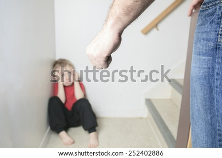 Boy sitting alone leaning on the wall - stock photo