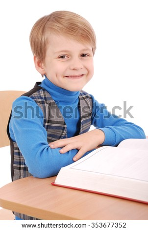 Boy sitting at a school desk isolated on white - stock photo