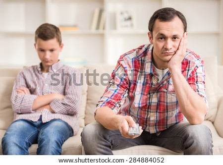 Boy sitting at sofa and get bored while his father watching television. - stock photo