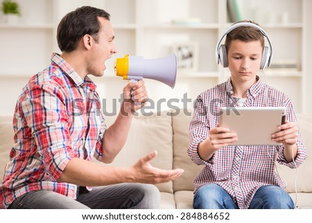 Boy sitting at sofa and using digital tablet while his father shouting to him. - stock photo