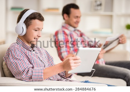 Boy sitting at sofa at home and listen to music while his father reading newspaper. - stock photo