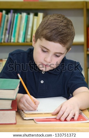 Boy sitting at table in library taking notes for school