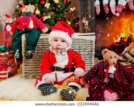 boy sitting at the Christmas decoration Christmas tree - stock photo