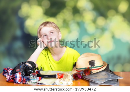 Boy sitting by the table and dreaming of beach vacations - stock photo
