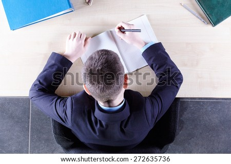 Boy sitting in a chair at the office table. Top view - stock photo