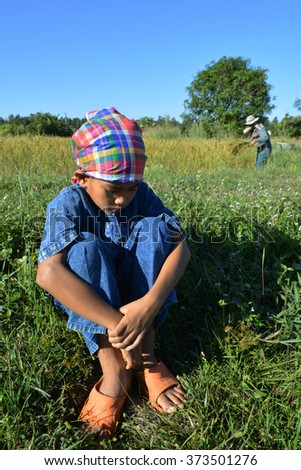 Boy sitting in a field . farmer is sad about his low price farmland product - stock photo