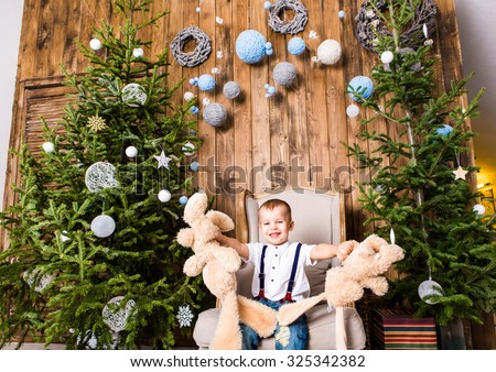 Boy  sitting in  chair near Christmas tree and gifts - stock photo