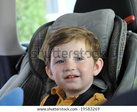 boy sitting in child car seat. shallow DOF - stock photo