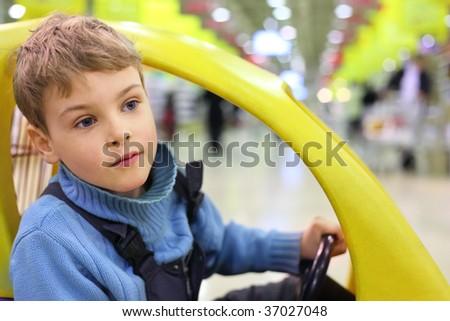 boy sitting in market wagon - stock photo