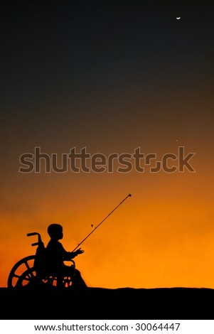 Boy sitting in wheel chair fishing at sunset - stock photo