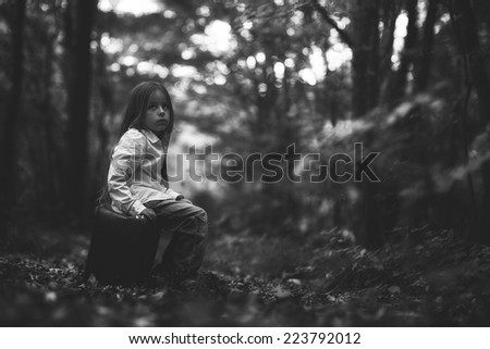 boy sitting on a suitcase in a dense forest in autumn