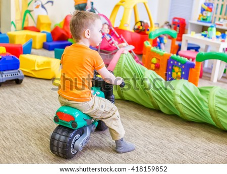 boy sitting on a toy motorcycle. child playing in a room with a lot of scattered toys - stock photo