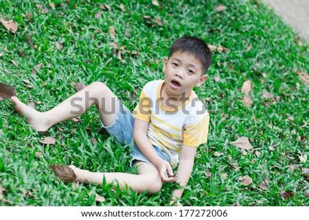 Boy sitting on grass - stock photo