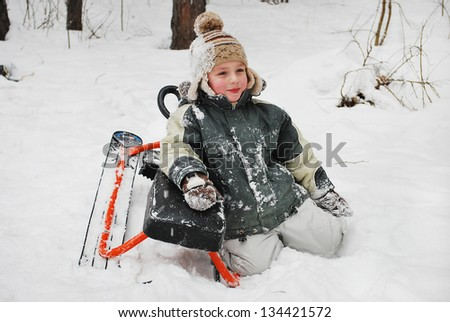 Boy sitting on snow with a sledge, winter cold day in the woods. - stock photo