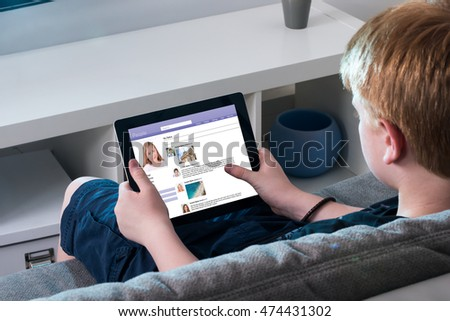 Boy Sitting On Sofa Using Social Networking Site On Digital Tablet At Home