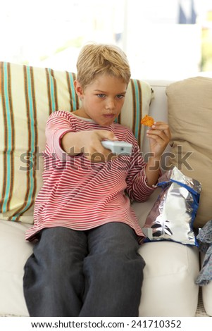 Boy sitting on sofa watching tv at home