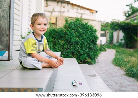 Boy sitting on stairs in back of  his house smiling